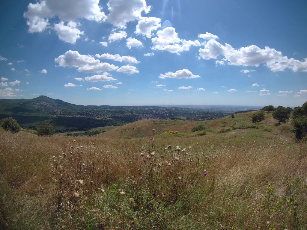 Photo of hilly landscape below a blue sky with scudding clouds.